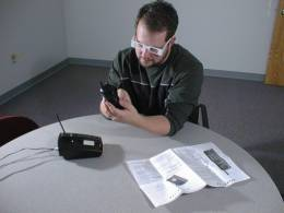 A test subject wearing low vision simulation glasses attempts to dial a telephone.