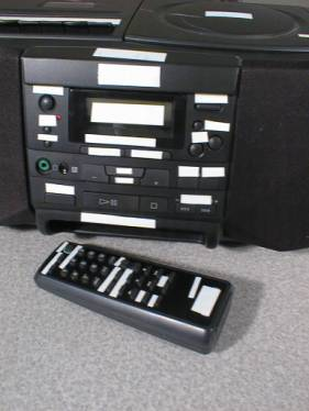 An image of a stereo and remote control with white tape over all of the buttons and printed labels.